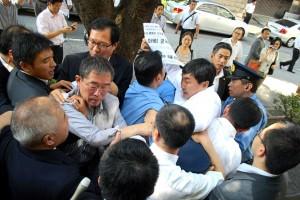 警官隊に車に押し込められようとする李鍾杰議員(ビラを手にした人)。(撮影/編集部)