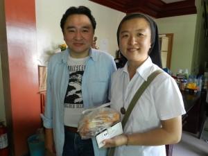 【中】学校に支援物資を届けた菅野さん(左)とシスター・チャン先生。
