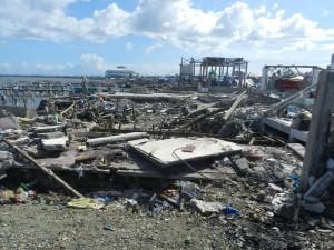 【上】パロ地区の漁港。水上の木造家屋は全壊し、遠くに避難所のコンベンションセンターが見える。