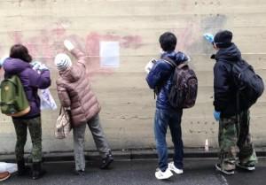 らくがきを黙々と消す「差別らくがき消し隊」のメンバーら(撮影/写真・岩崎眞美子)。