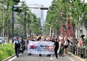 「仲良くしようぜパレード2014」と書かれた横断幕を持ち、大阪市内を行進するパレード隊。スタート地点では、隊列の最後尾が見えないほど、多くの参加者が歩道を埋め尽くしていた。(撮影/松岡瑛理)