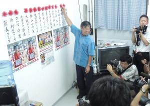 9月7日に投開票された名護市議選挙で与党当選者氏名に花をつける稲嶺進市長。(撮影/本誌取材班)