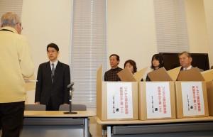 国交省職員に異議申立て書を手渡す市民団体メンバー(左)。(写真/樫田秀樹)