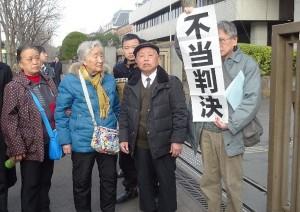 請求棄却に憤る栗遠奎原告団長(右から二人目)ら。2月25日、東京地裁前。(撮影/鈴木賢士)
