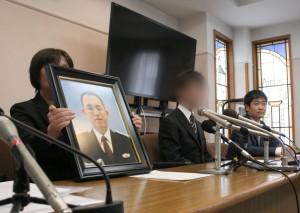 死亡した佐々木俊一巡査の遺影を手に記者会見する遺族と弁護士。(6月29日、撮影/三宅勝久)