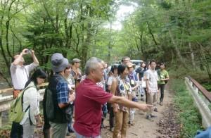 最終処分場候補地の栃木県塩谷町で役場の人(中央)から説明を受ける見学者。9月10日。(写真/みかみめぐる)