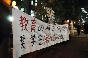 財務省前でローソクを灯して給付型奨学金導入を訴える人々。(撮影/樫田秀樹)